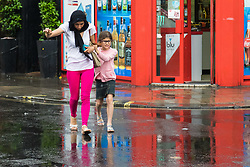 Soho, London, June 2nd 2017. A woman and child dash across the street through the rain as one of the thunderstorms predicted by the Met Office passes over Old Compton Street in Soho, London.