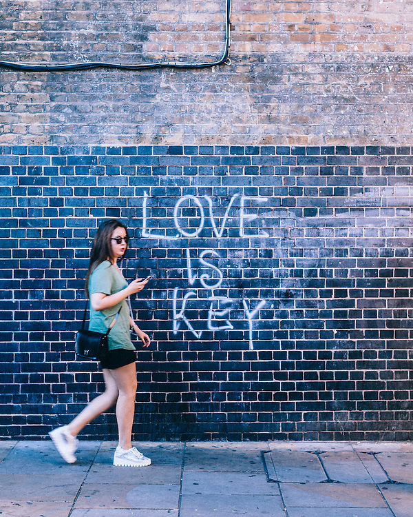 """A female walking past a graffity """"love is key"""" and texting on brick lane"""