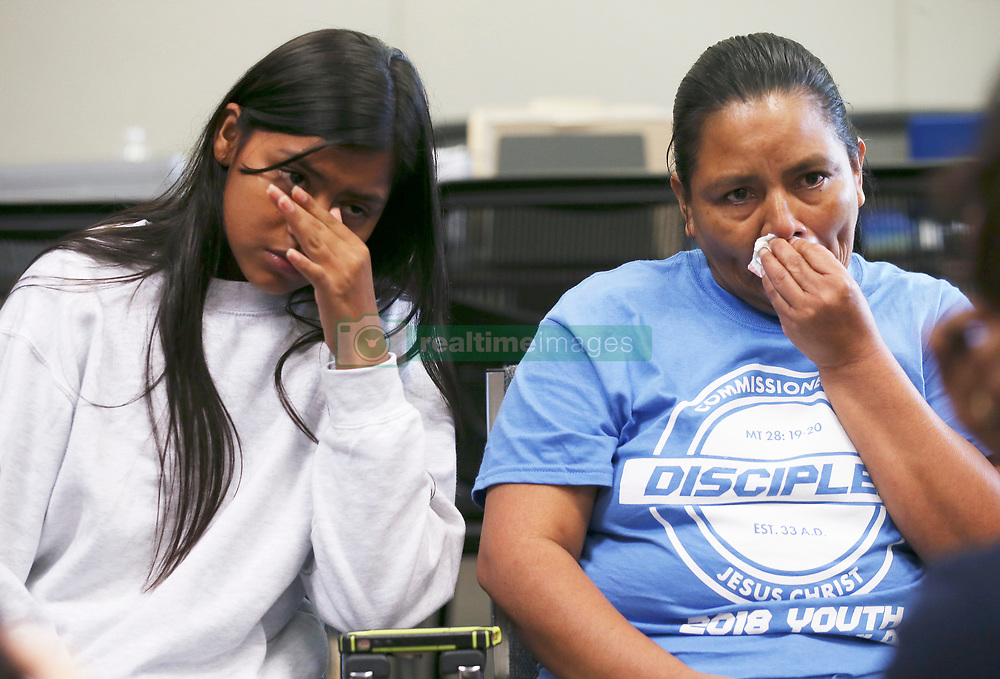July 26, 2018 - San Antonio, Texas, U.S. - SANDRA ELIZABETH SANCHEZ, 44,and her daughter, CRISTHEL NOHELIA BARAHONA SANCHEZ, 15, wipe tears while talking with media at the Archdiocese of San Antonio Catholic Charities offices, Thursday. Sanchez was recounting her separation from her daughter after being caught by U.S. Border Patrol in Eagle Pass on June 18th. Sanchez reunited with her daughter Wednesday night after they were released and are headed to Washington State where her older daughter and three grandchildren live. Three days before they were caught, Cristhel celebrated her 15th birthday along the route in Mexico. People around them pitched in and bought her a little birthday 'pastelito'. (Credit Image: © Jerry Lara/San Antonio Express-News via ZUMA Wire)