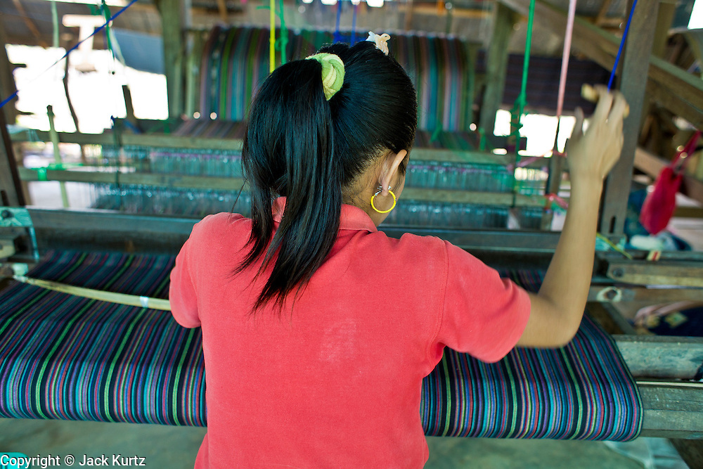 "19 FEBRUARY 2008 -- SANGKLABURI, KANCHANABURI, THAILAND: NGE, a Burmese refugee from the Mon hill tribe, works in the weaving shop at the Baan Unrak Children's Home in Sangklaburi, Thailand. Baan Unrak children's home and school, established in 1991 in Sangklaburi, Thailand, gives destitute children and mothers a home and career training for a better future. Baan Unrak, the ""Home of Joy,"" provides basic needs to well over 100 children, and  abandoned mothers. The home is funded by donations and the proceeds from the weaving and sewing shops at the home. The home is a few kilometers from the Burmese border. All of the women and children at the home are refugees from political violence and extreme poverty in Burma, most are Karen hill tribe people, the others are Mon hill tribe people. The home was started in 1991 when Didi Devamala went to Sangklaburi to start an agricultural project. An abandoned wife asked Devmala to help her take care of her child. Devmala took the child in and soon other Burmese women approached her looking for help.    Photo by Jack Kurtz"