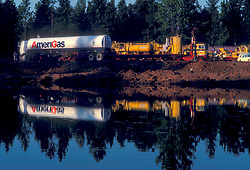 Large liquid transport truck parked at a work site reflecting in a pond