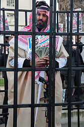 London, UK. 26th March, 2019. A man dressed as Mohammed bin Salman, Crown Prince of Saudi Arabia, stands in a cage among human rights campaigners from several different groups including Stop The War Coalition and Campaign Against the Arms Trade protesting opposite Downing Street against British arms sales to Saudi Arabia used to wage a 4-year war in Yemen. According to charity Save The Children, an estimated 85,000 children under the age of five may have died from acute malnutrition since the war began in 2015 and 14 million Yemenis are believed to face the risk of famine; according to the United Nations, millions of citizens have been displaced, over 56,000 Yemenis have been killed and the country is facing the 'world's worst humanitarian crisis'.