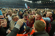Fabian Delph, the Aston Villa captain and goalscorer ©  is helped off the pitch by Stewards as Aston Villa fans celebrate during a pitch invasion after the game. Fabian Delph claimed afterwards that while being helped off fans were so close that he was bitten and some fans tried to remove his boot. The FA cup, 6th round match, Aston Villa v West Bromwich Albion at Villa Park in Birmingham, Midlands on Saturday 7th March 2015<br /> pic by John Patrick Fletcher, Andrew Orchard sports photography.