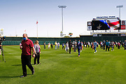 17 SEPTEMBER 2020 - DES MOINES, IOWA: People walk off the field after a naturalization ceremony at Principal Park, a minor league baseball stadium in downtown Des Moines. About 75 people from 32 countries were naturalized as US citizens Thursday. It was the last citizenship ceremony in Des Moines before citizenship fees dramatically increase. Starting Oct. 2, the fee to apply for U.S. citizenship will increase from $640 to $1,160 if filed online, or $ 1,170 in paper filing, a more than 80% increase in cost. Advocates for immigration are afraid the new fees will be too expensive for many immigrants and say it's an effort by the Trump Administration to limit the number of new citizens welcomed into the United States. Because of the COVID-19 pandemic, there has been dramatic slow down in the number of naturalization ceremonies this year.            PHOTO BY JACK KURTZ