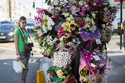 © licensed to London News Pictures. London, UK 26/08/2013. People looking at a floral memorial to nursery teacher Sabrina Moss who was shot dead in Kilburn while out celebrating her 24th birthday. Photo credit: Tolga Akmen/LNP