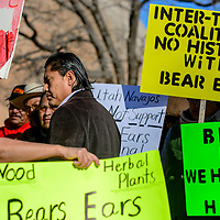 Protestors surround Co-Chair of the Bears Ears Inter-Tribal Coalition Eric Descheenie at the Navajo Nation Tribal Council chambers in Window Rock Monday.