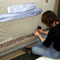 Asia, China, Beijing. Silk Carpet Weaver and loom