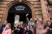 English writer Stella Duffy waves to a passing motorist while speaking passionately to a crowd outside Carnegie Library in Herne Hill. Faced with the closure of its beloved local library, the people of Lambeth, south London hold a demonstration outside the Edwardian-era building. Lambeth council plan to close the facility used by the community as part of austerity cuts, saying they will convert the building into a gym and privately-owned gentrified businesses - rather than a much-loved reading and learning resource. £12,600 was donated by the American philanthropist Andrew Carnegie to help build the library which opened in 1906. It is a fine example of Edwardian civic architecture, built with red Flettan bricks and terracotta, listed as Grade II in 1981.