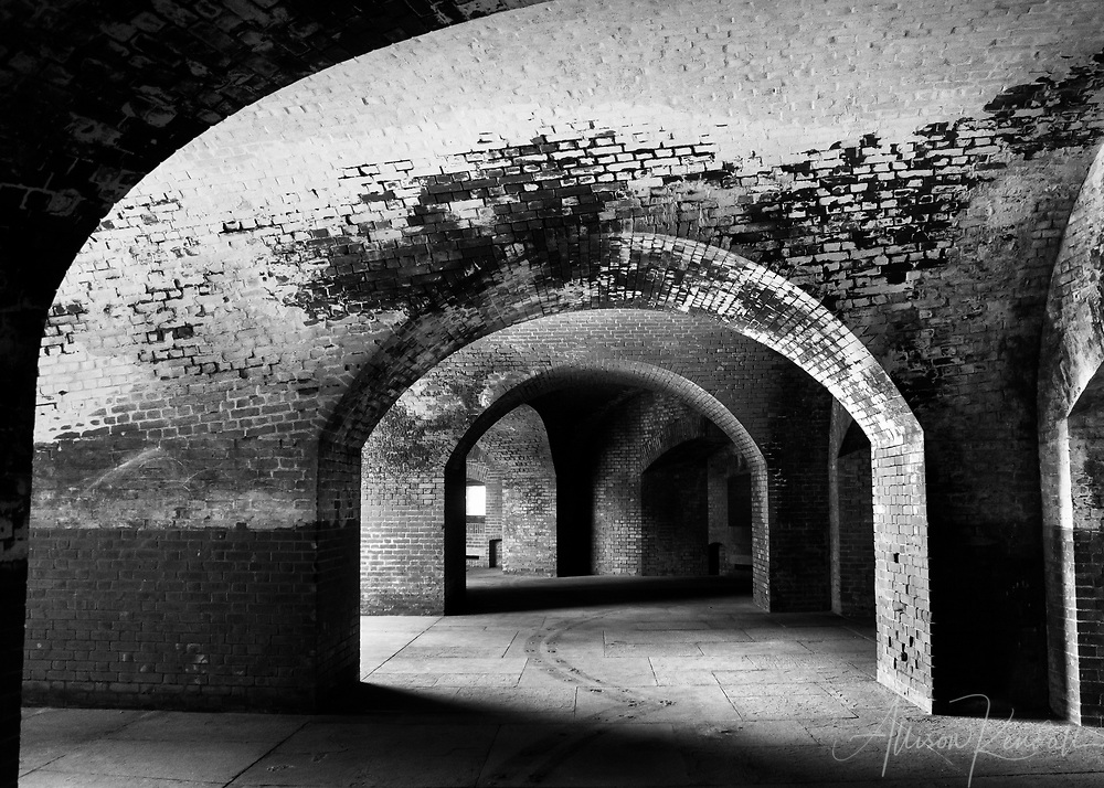 """Black and white architectural study of Fort Point, San Francisco; arches, windows and textural brick elements seen in varying degrees of light and shadow 