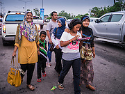 08 JULY 2013 - PATTANI, PATTANI, THAILAND:  A Thai Muslim family in Pattani walks to a restaurant Monday afternoon, the day before Ramadan. Ramadan starts July 9 and Monday was the last day observant Muslims were able to eat and drink during daylight hours. Muslims fast during the holy month of Ramadan, taking breakfast before dawn and not eating again until after sunset. The restaurants in Pattani, a Muslim majority city in southern Thailand, were packed Monday afternoon and evening.   PHOTO BY JACK KURTZ