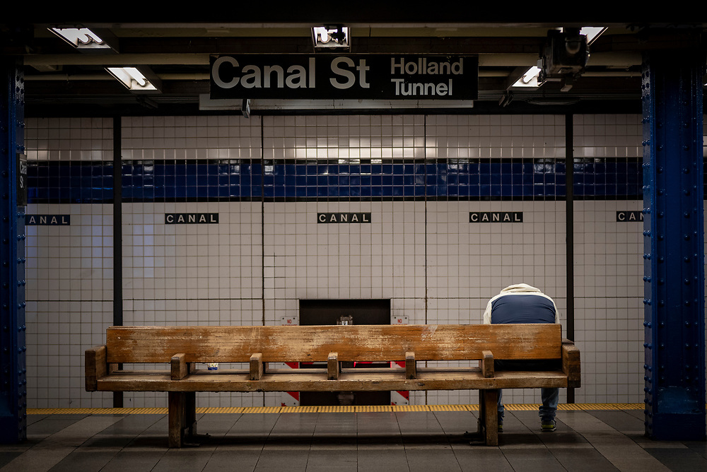 A commuter waits for a train at the Canal Street subway station in New York City. Due to the coronavirus pandemic, ridership in the subway station was greatly reduced. (March 20, 2020)