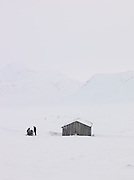 People on snow mobile stop beside a wooden hut in the frozen landscape of Spitsbergen. Spitsbergen is the largest island of the arctic archipelago Svalbard, of Norway