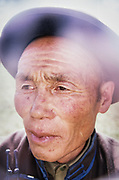 Portrait of a nomadic Mongolian herder wearing a bowler hat.