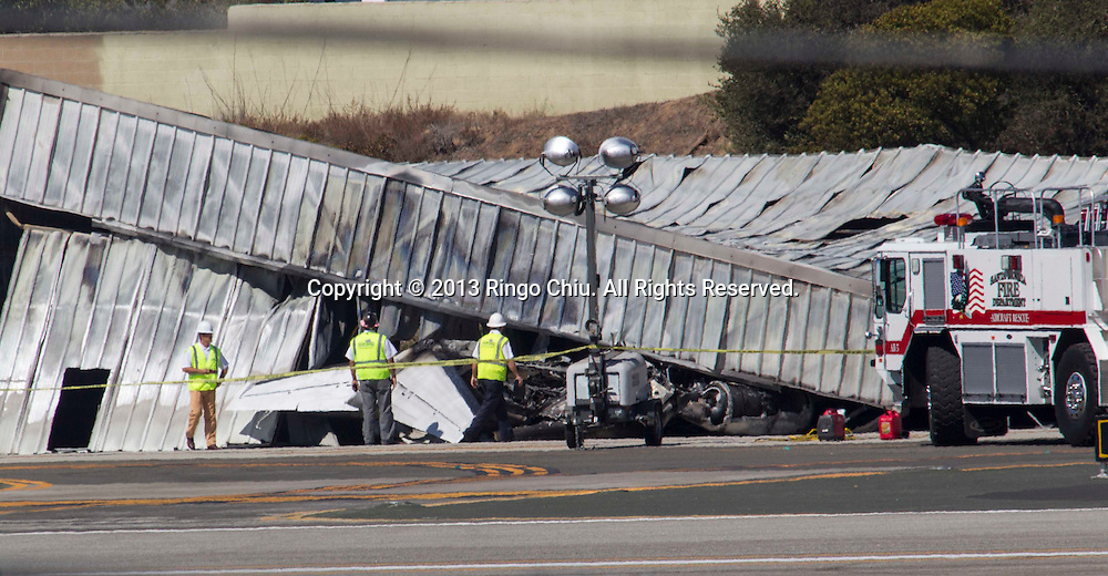The tail of a plane is visible as airport officials and investigators stand near a collapsed hangar at the site of a plane crash in Santa Monica, California on Monday, September 30, 2013. A twin-engine Cessna Citation jet flying in fromIdaho crashed into a hangar after landing at Santa Monica Airport  and veering off the runway, causing the structure to collapse, sparking an explosive fire and killing all aboard around 6:20PM, Sunday.  (Photo by Ringo Chiu/PHOTOFORMULA.com)