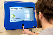 A prisoner uses his finger print to log in securely to a Unilink Self service kiosk allowing prisoners to manage their own life using biometrics while inside, giving them a bit more responsibility and control of their life. This system is used across the prison sector both public and private, HMP Wandsworth, London, United Kingdom. (Picture by Andy Aitchison)