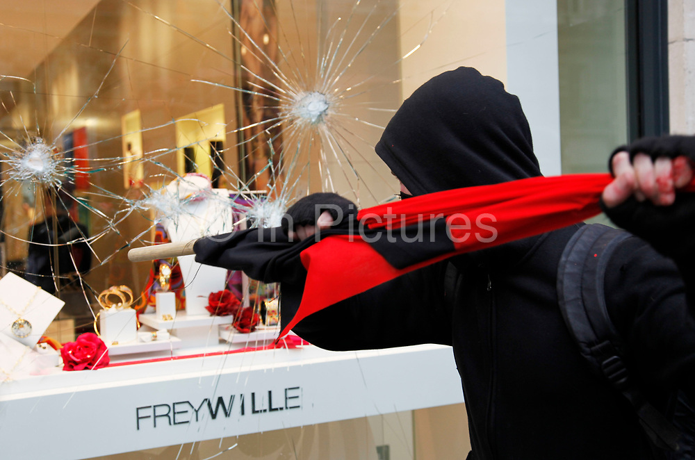 A jewellers on Piccadilly has it's windows broken by a protester. Anti capitalists / anarchists go on the rampage through central London on the back of the peaceful TUC protest march. The masked demonstrators ran a twisting route through the capital confusing the police and creating a situation which was very difficult to manage. The protesters attacked banks, shops and hotels, and the police in riot gear fought  face to face with them as they were pelted with ammonia, paint and fireworks loaded with coins.