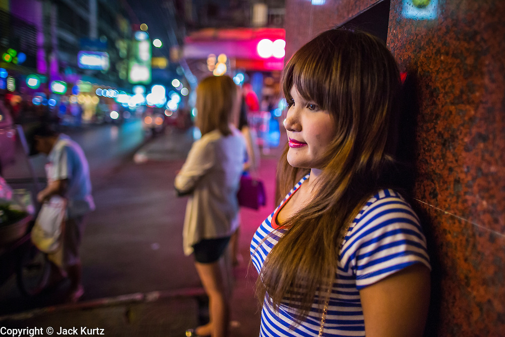 """21 JANUARY 2013 - BANGKOK, THAILAND: A sex worker waits for a client in front of the Nana Entertainment Plaza, a red light district in Bangkok. Prostitution in Thailand is technically illegal, although in practice it is tolerated and partly regulated. Prostitution is practiced openly throughout the country. The number of prostitutes is difficult to determine, estimates vary widely. Since the Vietnam War, Thailand has gained international notoriety among travelers from many countries as a sex tourism destination. One estimate published in 2003 placed the trade at US$ 4.3 billion per year or about three percent of the Thai economy. It has been suggested that at least 10% of tourist dollars may be spent on the sex trade. According to a 2001 report by the World Health Organisation: """"There are between 150,000 and 200,000 sex workers (in Thailand).""""   PHOTO BY JACK KURTZ"""