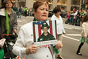 A woman bears a card in memory of firefighter Brian G. McAleese, of Engine Company 226, whi died on 9/11.
