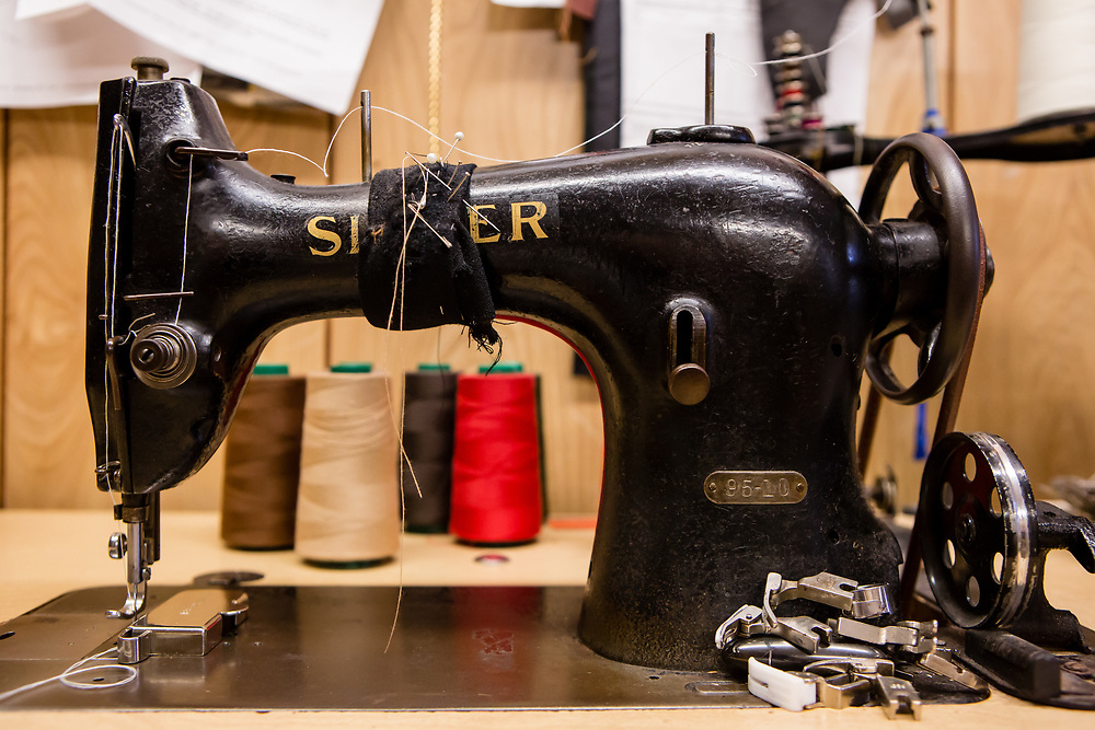 The sewing machines are mostly old Singers, with cast iron frames and mechanisms of machined metal—still durable, useful and repairable. Stacked on the table are a selection of specialty feet for the machine.