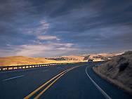 An unloaded logging truck climbs a highway grade in evening light near the Columbia River in the rural Klickitat County prairie.  In the distance is a line of electric generating windmills. Klickitat County. WA, USA