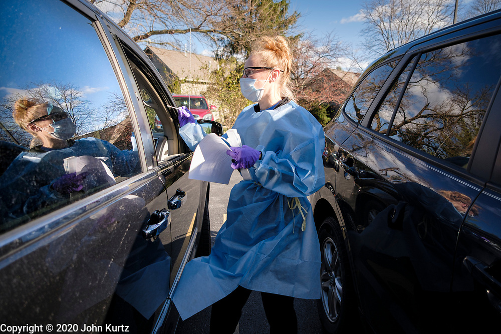 """15 NOVEMBER 2020 - WEST DES MOINES, IOWA: AMBER LINT swabs a patient during a drive up rapid COVID test in West Des Moines. Hundreds of people lined up for drive up COVID-19 tests at the Doctors NOW clinic in West Des Moines. Iowa is seeing a surge in COVID-19 (Coronavirus) cases and the state's """"Test Iowa"""" public testing program is swamped with some people waiting 3 - 5 days for an appointment for a drive up test. As of Sunday, 15 November, Iowa had the 3rd highest Coronavirus (SARS-CoV-2) infection rate in the country with 4,432 new cases reported in the previous 24 hours and 1,279 people hospitalized for COVID-19. Des Moines area hospitals have warned that they are at capacity and many hospitals are reporting staffing shortages because workers have come down with COVID-19.     PHOTO BY JACK KURTZ"""