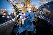 "15 NOVEMBER 2020 - WEST DES MOINES, IOWA: AMBER LINT swabs a patient during a drive up rapid COVID test in West Des Moines. Hundreds of people lined up for drive up COVID-19 tests at the Doctors NOW clinic in West Des Moines. Iowa is seeing a surge in COVID-19 (Coronavirus) cases and the state's ""Test Iowa"" public testing program is swamped with some people waiting 3 - 5 days for an appointment for a drive up test. As of Sunday, 15 November, Iowa had the 3rd highest Coronavirus (SARS-CoV-2) infection rate in the country with 4,432 new cases reported in the previous 24 hours and 1,279 people hospitalized for COVID-19. Des Moines area hospitals have warned that they are at capacity and many hospitals are reporting staffing shortages because workers have come down with COVID-19.     PHOTO BY JACK KURTZ"
