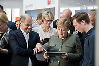 14 NOV 2018, POTSDAM/GERMANY:<br /> Olaf Scholz (L), SPD, Bundesfinanzminister, Anja Karliczek (M), MdB, CDU, Bundesministerin fuer Bildung und Forschung, Angela Merkel (R), CDU, Bundeskanzlerin, mit einem iPad, waehrend einer Praesentation des HPI im Rahmen der Klausurtagung des Bundeskabinetts, Hasso Plattner Institut (HPI), Potsdam-Babelsberg<br /> IMAGE: 20181114-01-094<br /> KEYWORDS; Kabinett, Klausur, Tagung, freundlich, fröhlich, froehlich