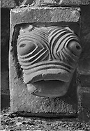 The Stone Bestiary - Black and white photo art print of Norman Romanesque exterior corbel no 41 - sculpture of a grotesque stylised creatures head with bulging eyes. The Norman Romanesque Church of St Mary and St David, Kilpeck Herefordshire, England. Built around 1140 .<br /> <br /> Visit our LANDSCAPE PHOTO ART PRINT COLLECTIONS for more wall art photos to browse https://funkystock.photoshelter.com/gallery-collection/Places-Landscape-Photo-art-Prints-by-Photographer-Paul-Williams/C00001WetsxVxNTo