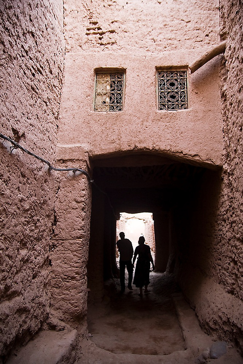 A man and woman walk through one of the many covered passageways in Ait Bounou, an ancient kasbah, or fortified village, in the Moroccan Sahara. The town is quickly falling into ruin as the inhabitants flee the drying well and the advancement of the dunes expedited by a 16-year drought and the damming of the Draa River.