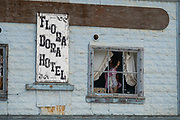 Despite the suggestive mannequin, the 1898 Flora Dora Hotel was unlikely a brothel. Dawson City was the center of the Klondike Gold Rush (1896–99), after which population rapidly declined, in Yukon, Canada. Dawson City shrank further during World War II after the Alaska Highway bypassed it 300 miles (480 km) to the south using Whitehorse as a hub. In 1953, Whitehorse replaced Dawson City as Yukon Territory's capital. Dawson City's population dropped to 600–900 through the 1960s-1970s, but later increased as high gold prices made modern placer mining operations profitable and tourism was promoted. In Yukon, the Klondike Highway is marked as Yukon Highway 2 to Dawson City.