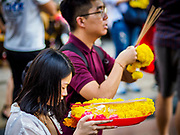 31 DECEMBER 2018 - BANGKOK, THAILAND: A woman prays before leaving an offering of marigolds at the Erawan Shrine in Bangkok. The shrine was packed with tourists and Thais praying and making merit on New Year's Eve. Many Thais go to temples to meditate and pray on New Year's Eve.    PHOTO BY JACK KURTZ