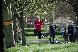 © Licensed to London News Pictures. 04/04/2020. London, UK. A man playing on a tightrope at Paddington Recreation Ground in London, during a pandemic outbreak of the Coronavirus COVID-19 disease.. The public have been told they can only leave their homes when absolutely essential, in an attempt to fight the spread of coronavirus COVID-19 disease. Photo credit: Ben Cawthra/LNP