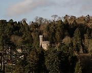 MERTHYR TYDFIL, WALES - 16th March 2020 - Cyfarthfa Castle peaking through the trees of the park, Merthyr Tydfil on a sunny day.