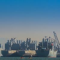 Kayakers paddle past naval transport ships anchored at docks at Alameda Naval Station, near Oakland, California.