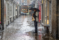 Licensed to London News Pictures. 17/05/2021. London, UK. A shopper gets caught in torrential rain in Richmond, south west London as the miserable May weather drags on. Today Government's roadmap out of lockdown continues with pubs, restaurants, cafes and bars able to serve customers inside. However Downing Street has warned that due to the Indian variant, local lockdowns could be quickly reintroduced in high risk areas. Photo credit: Alex Lentati/LNP