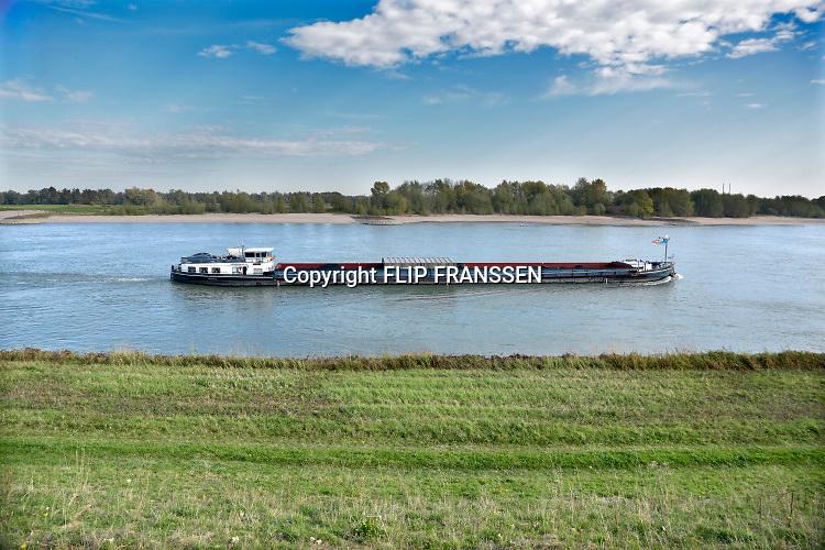 Nederland, Nijmegen, 15-10-2019 Een binnenvaartschip passeert de nevengeul in de waal ter hoogte van Nijmegen . De Waal is het Nederlandse deel van de Rijn en de belangrijkste vaarroute van en naar Rotterdam en Duitsland . Foto: Flip Franssen