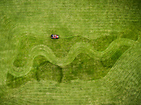 Aerial photography of man on lawnmower creating shapes in grass.