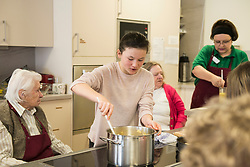Nurse with senior women and girls preparing food at rest home