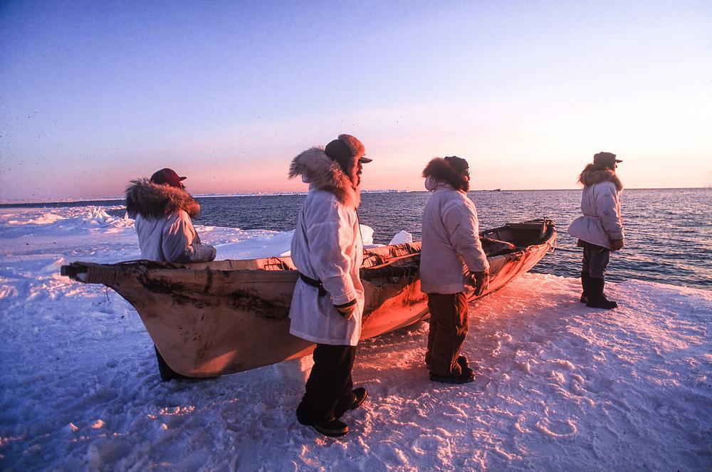 Sunset over a native whaling crew and their umiak on the frozen sea ice near Barrow, Alaska