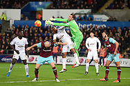 Adrian, the West Ham Utd goalkeeper punches clear from Andre Ayew of Swansea city .Barclays Premier league match, Swansea city v West Ham Utd at the Liberty Stadium in Swansea, South Wales  on Sunday 20th December 2015.<br /> pic by  Andrew Orchard, Andrew Orchard sports photography.