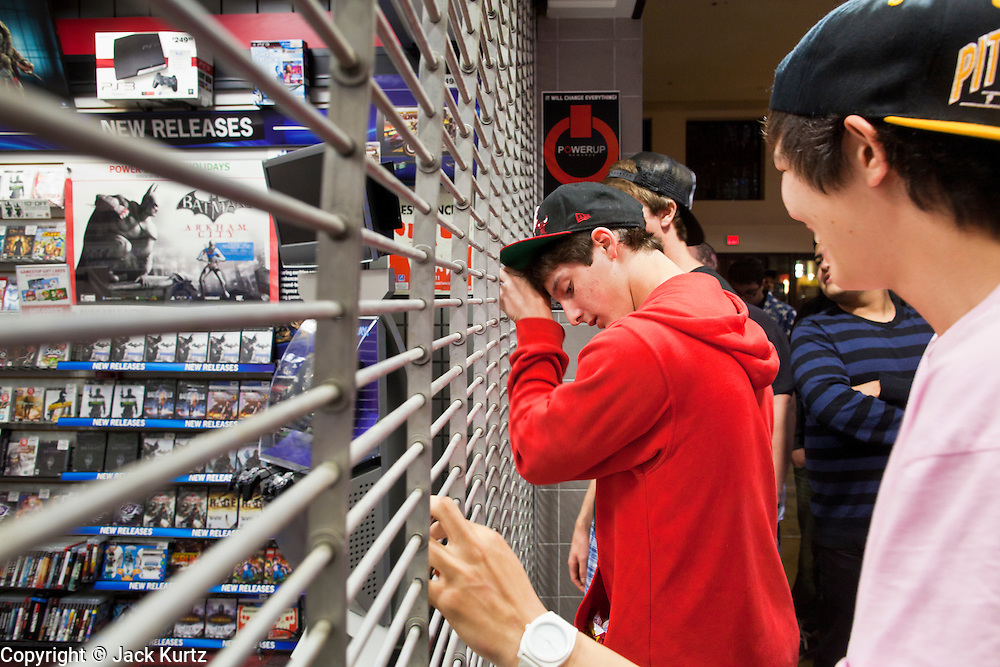 """24 NOVEMBER 2011 - PHOENIX, AZ:  Jack Nudo (CQ CENTER RED SHIRT), 17, and Drew Tsao, 17, (CQ RIGHT PINK SHIRT) both from Scottsdale wait for the Game Stop to open at Paradise Valley Mall Thursday. """"Black Friday,"""" the unofficial start of the holiday shopping season started even earlier than normal. Many stores, including Target and Best Buy, opened at midnight.    Photo by Jack Kurtz"""
