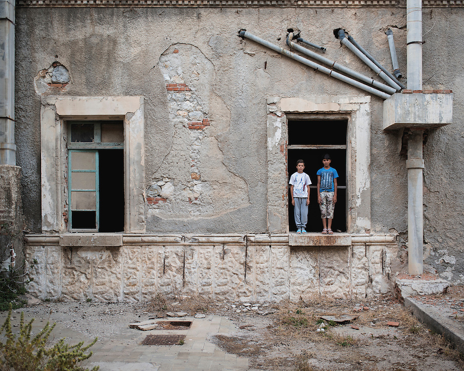 Kurdish refugee children, Youssef, 14, and Diar, 13, standing in a window at the abandoned Lepida psychiatric hospital, in whose grounds the Leros 'Hot spot' (an EU-run migrant's reception centre) has been built. <br /> <br /> Originally constructed, in 1930 by fascist Italy, as barracks for Italian soldiers serving in the aeronautical base of Portolago, it was then, for a short period after WWII, a re-education camp for the children of Greek Communists. In 1958, it was converted into the biggest psychiatric hospital in the country. The conditions for the patients were horrific and it was shut down in the late 1980s and the patients moved into smaller buildings in the grounds and elsewhere on the island