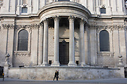 Two men walk beneath the tall pillars of St Paul's Cathedral, on the southern side of the Wren-designed church.