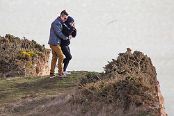 © Licensed to London News Pictures. 04/02/2018. Brighton, UK. Members of the public stand close to the edge of the Birling Gap and Beachy Head cliffs in windy conditions.  Photo credit: Hugo Michiels/LNP