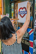 A wine stall holder puts up a sign of solidarity - The market reopening is signified by the ringing of the bell and is attended by Mayor Sadiq Khan. Tourists and locals soon flood back to bring the area back to life.