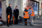 Bond Street guides holding orange-themed brolleys stand next to two construction site workmen.
