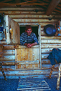 Dick Proenneke in dutch doors he handcrafted with spruce root hinges, Upper Twin Lake, Lake Clark National Park, Alaska.