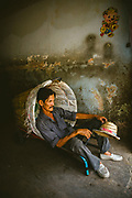 A porter taking a break from work, resting in the basket of his trolley inside a warehouse, Pak Khlong Talat, Bangkok, Thailand