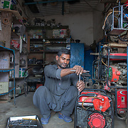 INDIVIDUAL(S) PHOTOGRAPHED: Saifullah. LOCATION: Bhance Colony, Landhi, Karachi, Pakistan. CAPTION: Saifulla repairs a generator at his workshop in Karachi, Pakistan. Since starting out 18 years ago from a small roadside generator repair shop, Saifulla has since expanded his business into spare parts thanks to 2012 a microfinancing loan of Rs. 40,000 (£280) from the First Micro Finance Bank (FMFB). He has now completed various cycles of financing and repayment. His most recent loan totalled Rs. 150,000, which allowed him to shift his business into a larger rented space and hire three more workers. Today, his monthly revenues average around Rs. 130,000, a sum that recently enabled him to buy an old 1000 cc car for his family. Saifullah dreams of one day owning an even bigger auto-repairing workshop that also offers generator sales.