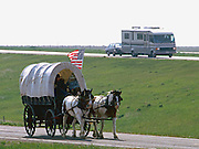 A recreational vehicle passes covered wagons and horseback riders on the modern South Dakota prairie outside Rapid City, South Dakota.